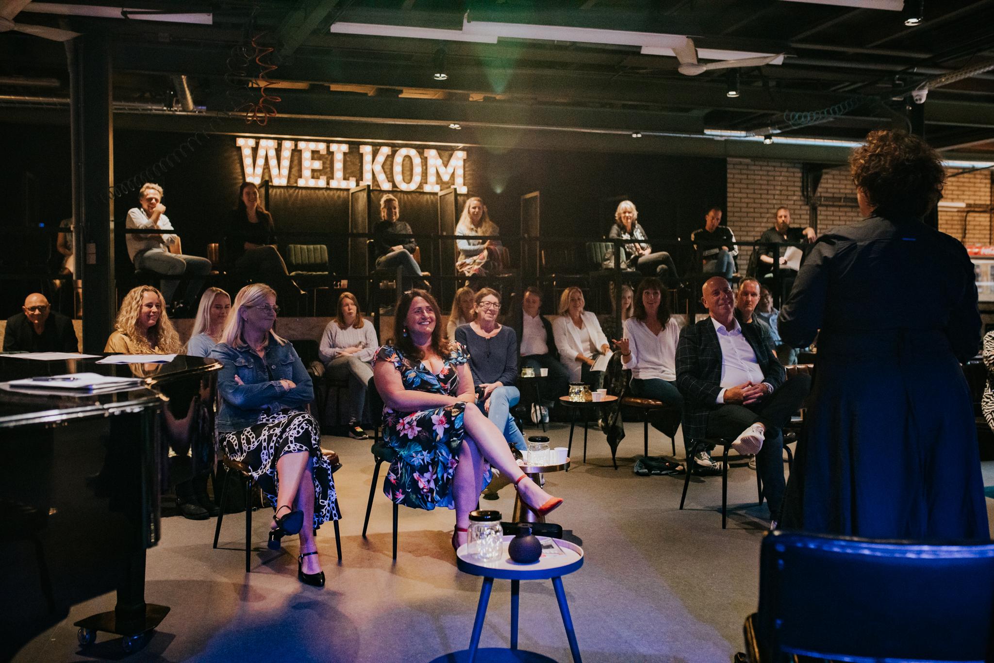 De deelnemers zitten in theater De Fabriek.